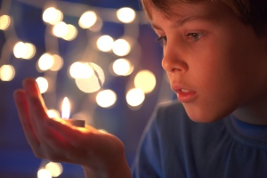 boy holds in a hand a burning candle against sparks